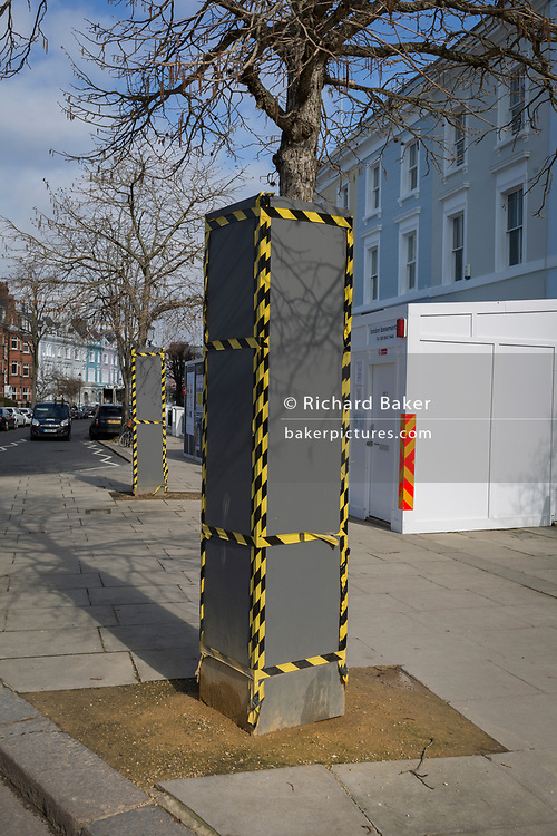 Tree protectors encased in a wrapping of wood with hazard tape on a street corner of Elgin Cresent and Clarendon Road W11 in Notting Hill in the Royal Borough of Kensington and Chelsea, on 13th March 2018, in London, England.