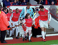 Martin Keown leads the team out with the Arsenal mascot. Arsenal v Derby County. FA Premiership 11/11/2000. Credit: Colorsport.
