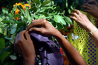 """MEXICO, Veracruz, Tantoyuca, Oct 27- Nov 4, 2009. Teachers help make an altar at Tantoyuca's Roberto Medellin primary school. """"Xantolo,"""" the Nahuatl word for """"Santos,"""" or holy, marks a week-long period during which the whole Huasteca region of northern Veracruz state prepares for """"Dia de los Muertos,"""" the Day of the Dead. For children on the nights of October 31st and adults on November 1st, there is costumed dancing in the streets, and a carnival atmosphere, while Mexican families also honor the yearly return of the souls of their relatives at home and in the graveyards, with flower-bedecked altars and the foods their loved ones preferred in life. Photographs for HOY by Jay Dunn."""