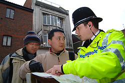 Policeman helping lost Japanese tourists find their way York UK