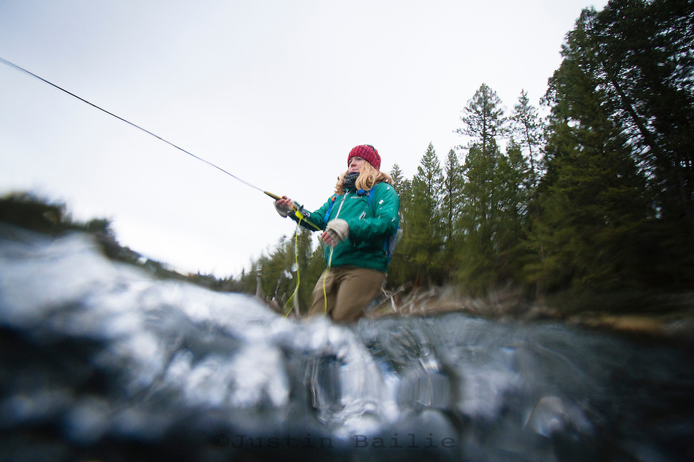 Young woman fly fishing in the Box Canyon section of the Henry's Fork of the Snake in NE Idaho.