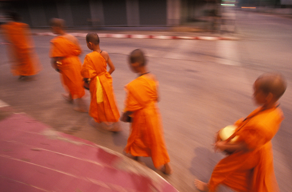 Novice monks walk the streets with their food bowls early in the morning, Mae Hong Son, Thailand. April 2003. People will stop them on the way to put food into their bowls as an offering.