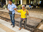 19 MARCH 2015 - AYUTTHAYA, AYUTTHAYA, THAILAND:   A taxi driver helps a blind man to the platform to catch the train from Ayutthaya to Bangkok. The train line from Bangkok to Ayutthaya was the first rail built in Thailand and was opened in 1892. The State Railways of Thailand (SRT), established in 1890, operates 4,043 kilometers of meter gauge track that reaches most parts of Thailand. Much of the track and many of the trains are poorly maintained and trains frequently run late. Accidents and mishaps are also commonplace. Successive governments, including the current military government, have promised to upgrade rail services. The military government has signed contracts with China to upgrade rail lines and bring high speed rail to Thailand. Japan has also expressed an interest in working on the Thai train system. Third class train travel is very inexpensive. Many lines are free for Thai citizens and even lines that aren't free are only a few Baht. Many third class tickets are under the equivalent of a dollar. Third class cars are not air-conditioned.   PHOTO BY JACK KURTZ