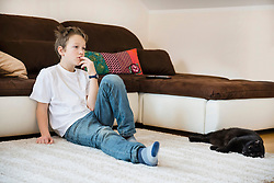 Boy sitting in living room with cat