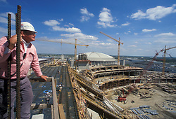 Stock photo of a man standing atop the construction site of Houston's Reliant Stadium near downtown Houston Texas