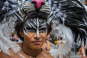 A man wears a black and white feathered headdress in the parade on 5th Avenue.