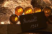 In the underground wine cellar: lying bottles in the treasure chamber where the oldest bottles are kept old bottles of Meursault 1967. White Burgundy wine vaulted vault ceiling with contrasting lights. Backlit backlight back light lit, Maison Louis Jadot, Beaune Côte Cote d Or Bourgogne Burgundy Burgundian France French Europe European