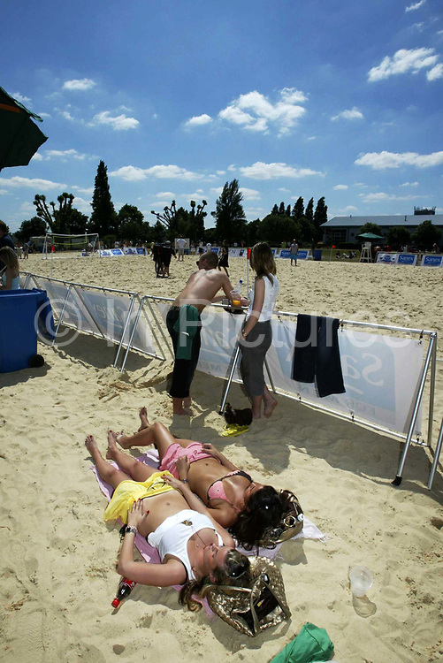 Laying out sunbathing on the sand. St Georges Park Wandsworth, South West London, as part of the Sanex Urban Beach Party.