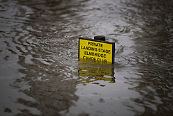 © Licensed to London News Pictures. 01/02/2021. Weybridge, UK. A sign submerged in flood water on the river Thames at Weybridge in Surrey. Flood defences are bing installed in the area because In 2014 Weybridge and the surrounding area was badly hit by flooding. Photo credit: Ben Cawthra/LNP