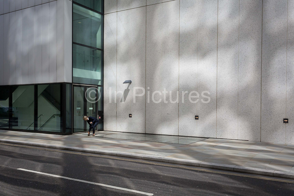Beneath reflected light on a wall near the Barbican, a woman bends down to adjust her shoe in the City of London, the capitals financial district - aka the Square Mile, on 8th August, in London, England.