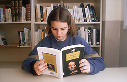 Young girl reading book in school library with bookcase behind her,