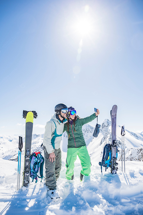 Couple of skiers doing a selfie photograph at the top of the mountain on a beautiful day