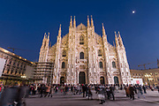 Crowds of people walk in front of the Cathedral in Piazza del Duomo as night falls in central Milan on 7th December 2008 in Milan, Italy. The cathedral, or duomo took six centuries to build and occupies the heart of the city, and attracts visitors from all over the world.
