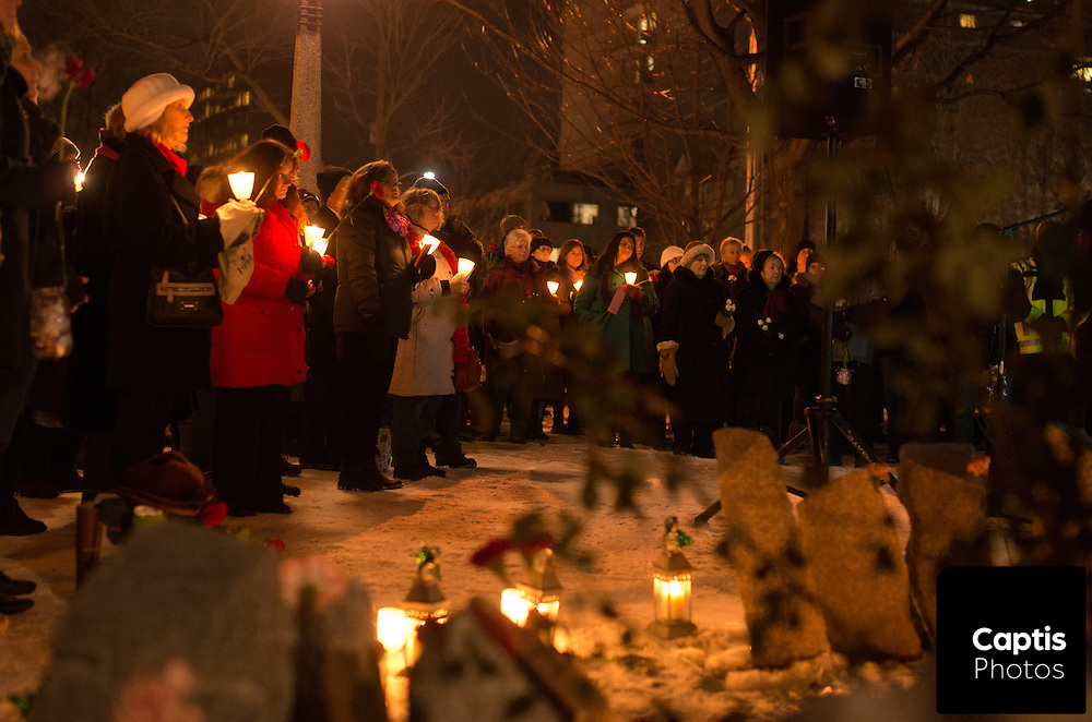 People hold candles near the Women's Monument in Minto Park during the vigil. December 6, 2014.