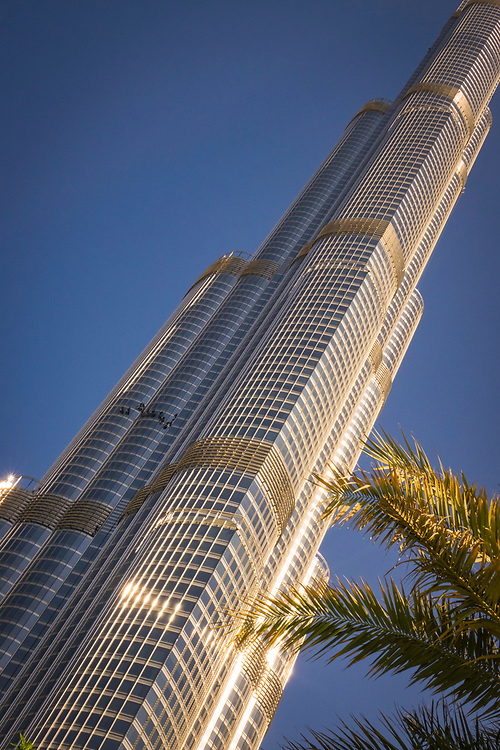 Low angle view of the famous Burj Khalifa, the tallest building in the world, as of 2021 in Dubai, United Arab Emirates with trees in the foreground and window washers halfway up the tower