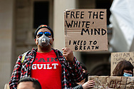 A protester wearing a facemask holds up a sign during a Black Lives Mater rally on 06 June, 2020 in Melbourne, Australia. This event was organised to rally against aboriginal deaths in custody in Australia as well as in unity with protests across the United States following the killing of an unarmed black man George Floyd at the hands of a police officer in Minneapolis, Minnesota. (Photo by Dave Hewison/ Speed Media)