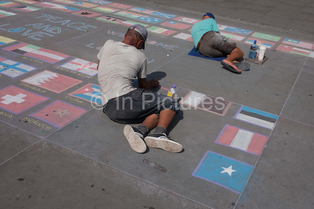 Street artists lay on the ground each drawing in chalk the flags of the world on the pavement, on 24th August 2016, in Trafalgar Square, London UK. Sketching the national flags of other nations, they hope to attract visitors to the capitals landmark who might give them some spare cash.