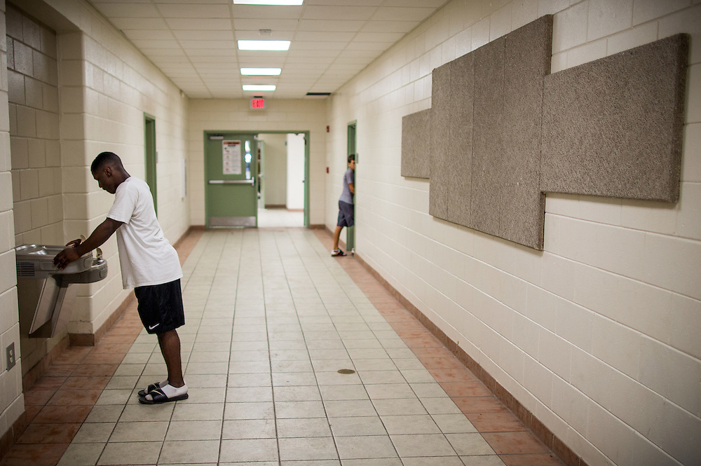BEAUFORT, SC - JULY 14: CJ Cummings takes a break for water  on July 14, 2014 in the hallway of the Beaufort Middle School in Beaufort, South Carolina. The 14-year-old will attempt to break the U.S. record for the clean and jerk lift of 152.5 kg (336 pounds) when he competes at the Open Men's Nationals later this month. (Photo by Stephen B. Morton for The Washington Post)