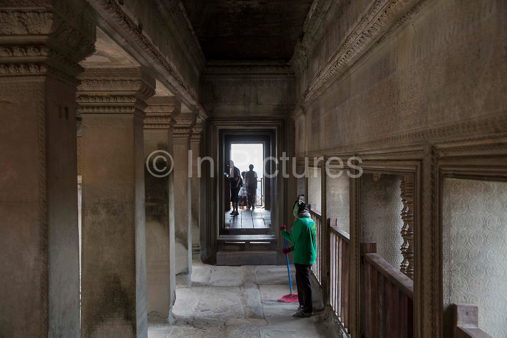 A woman sweeps her cleaning brush along the walkway within the ancient temple  of Angkor Wat Siem Reap, Cambodia.  Angkor Wat is one of UNESCO's world heritage sites. It was built in the 12th century and is Cambodia's main tourist destination. Tourists explore the site in the background.
