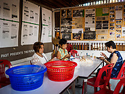 21 MARCH 2017 - BANGKOK, THAILAND: Women make paper flowers for use in Buddhist rituals in a community building in Pom Mahakan. They are among the last people living in the old fort. The final evictions of the remaining families in Pom Mahakan, a slum community in a 19th century fort in Bangkok, have started. City officials are moving the residents out of the fort. NGOs and historic preservation organizations protested the city's action but city officials did not relent and started evicting the remaining families in early March.               PHOTO BY JACK KURTZ