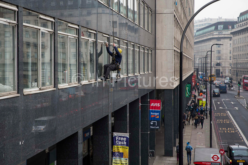 An abseiling window cleaner cleaning the windows of the office block at number 11 York Rd, next to Waterloo train station in Lambeth, London.