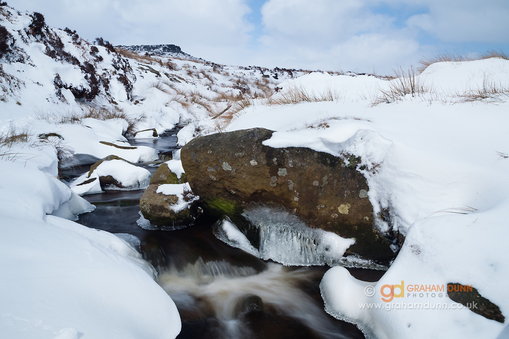 Early spring snow and ice at Burbage Brook. Overlooked by Carl Wark. Peak District, Derbyshire, England, UK.
