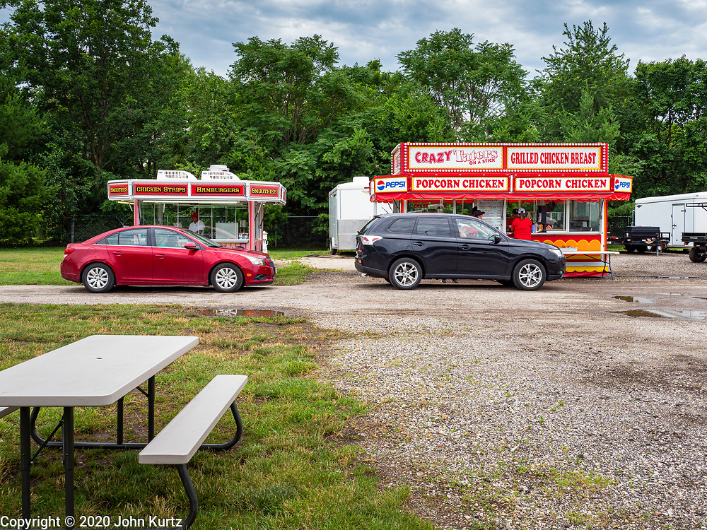 """26 JUNE 2020 - DES MOINES, IOWA: An empty picnic table at Fair Food Friday in Des Moines. The 2020 Iowa State Fair, like many state fairs in the Midwest, has been cancelled this year because of the COVID-19 (Coronavirus) pandemic. The cancellation of the fair left many small vendors stranded with no income. Some of the fair food vendors in Iowa started """"Fair Food Fridays"""" on a property a few miles south of the State Fairgrounds. People drive up and don't leave their cars while vendors bring them the usual midway fare; corndogs, fried tenderloin sandwiches, turkey legs, deep fried Oreos, lemonaide and smoothies. Fair Food Friday has been very successful. The vendors serve 450-500 people per Friday and during the lunch rush people wait in line in their cars 30 - 45 minutes to place an order.      PHOTO BY JACK KURTZ"""