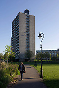 A woman walks along a path under high-rise flats in Kennington Park, Lambeth, South London. The three blocks of flats (apartments) are multi-storey and house poorer south London families. Kennington Park is in Kennington in London, England, and lies between Kennington Park Road and St Agnes Place. It was opened in 1854. Previously the site had been Kennington Common. This is where the Chartists gathered for their biggest 'monster rally' on 10 April 1848. Soon after this demonstration the common was enclosed and, sponsored by the royals, made into a public park. Kennington Common was a site of public executions until 1800 as well as being the South London's area of Public speaking. Some of the most illustrious orators to speak here were Methodist founders George Whitefield and John Wesley who is reputed to have attracted a crowd of 30,000.