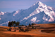 PERU, HIGHLAND, ANDES MOUNTAINS the Cordillera de Urubamba Mountains rises above farmland and adobe farm houses at Maras near Cuzco