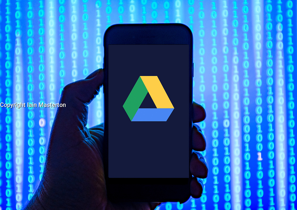 Person holding smart phone with  Google Drive cloud storage logo displayed on the screen. EDITORIAL USE ONLY