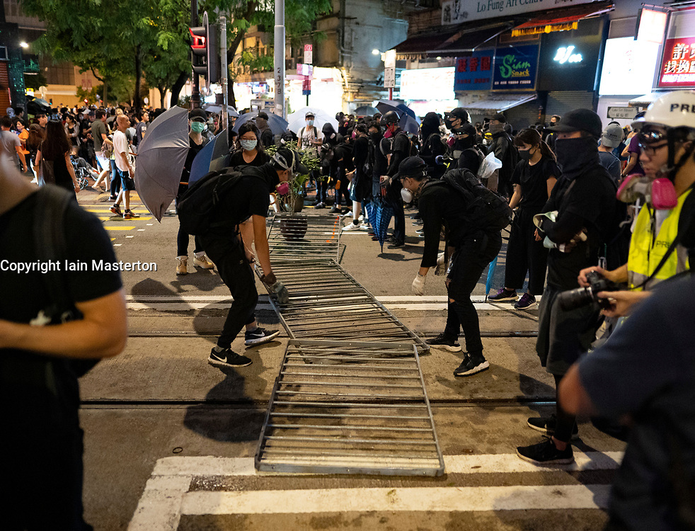 Hong Kong. 6 October 2019. Tens of thousands of pro-democracy protestors march in pouring rain through centre of Hong Kong today from Causeway Bay to Central. Peaceful march later turned violent as a hard-core of protestors confronted police. Pic; Protestors build small barricade in street in Tin Hau. Iain Masterton/Alamy Live News.