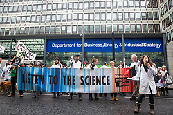 London, UK. 22 November, 2019. Dr Emily Grossman addresses climate activists from Scientists for XR outside the Department for Business, Energy and Industrial Strategy during a demonstration intended to communicate the science relating to the climate and ecological emergency. Activists were dressed in labcoats to represent the 1600 scientists worldwide who have signed the Scientists Declaration in support of non-violent direct action against government inaction against the climate and ecological emergency.