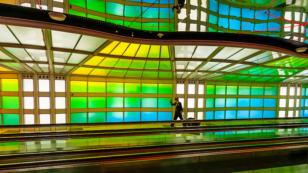 """A female airline pilot walks through the tunnel, passing """"Sky's the Limit"""" by artist Michael Hayden at O'Hare International Airport, Chicago, Illinois USA."""