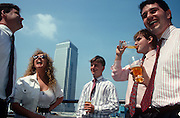 In the shadow of 1 Canada Square, the iconic Canary Wharf tower in London's Docklands stands as an icon for Thatcherite Britain when the good times, prosperity and economic upturns seemed unshakeable. Four work colleagues stand under a hot lunchtime sun during a summer heatwave. In their shirtsleeves the men each hold pints of refreshing lager, all having removed their dark jackets to enjoy the company of a flirtatious female who appears to be flirting with an older male companion. The sky is blue and the five are care-free to any future economic uncertainty.