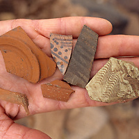 An archaeologist holds ancient Nabatean pottery shards he found in Jordan's mysterious Petra.