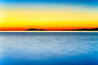 Sunset, Iona Park:  Distant coastal islands are held in silhouette under orange-red sunset, with the blue Pacific captured in this long exposure, Richmond British Columbia Canada.