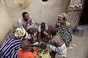 Members of the Natomo household sit around their communal dinner of fish and rice. The Natomo family lives in two mud brick houses in the village of Kouakourou, Mali, on the banks of the Niger River. Material World Project.