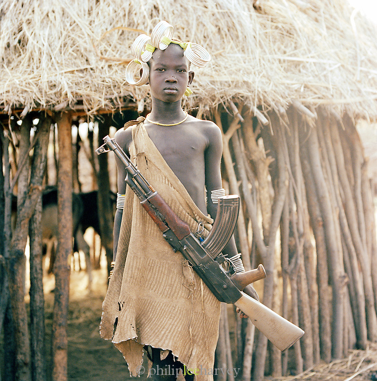 Mursi tribal boy poses with an AK-47, Omo Valley, Southern Ethiopia.