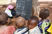 Abdulai Sadia teaches children under a tree in the community of Kunayili, near Gushegu, Northern Ghana, on Wednesday November 2, 2011. Sadia first started teaching children under a tree before community members helped her build a proper school.