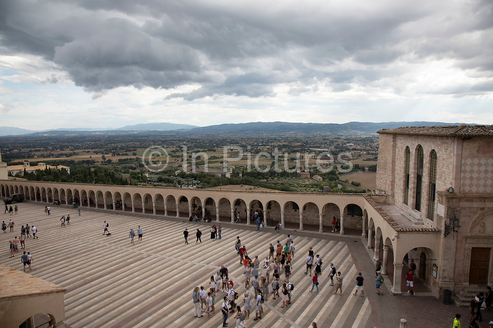 Tourists at the Piazza Inferiore di San Francesco at the Basilica of San Francesco dAssisi in Assisi, Umbria, Italy. The Papal Basilica of Saint Francis of Assisi is the mother church of the Roman Catholic Order of Friars Minor Conventual in Assisi, a town of Umbria region in central Italy, where Saint Francis was born and died. The basilica is one of the most important places of Christian pilgrimage in Italy. Assisi is a town in the Province of Perugia in the Umbria region, on the western flank of Monte Subasio. It is generally regarded as the birthplace of the Latin poet Propertius, and is the birthplace of St. Francis, who founded the Franciscan religious order in the town in 1208, and St. Clare, Chiara dOffreducci, the founder of the Poor Sisters, which later became the Order of Poor Clares after her death. Assisi is now a major tourist destination for those sightseeing or for more religious reasons.