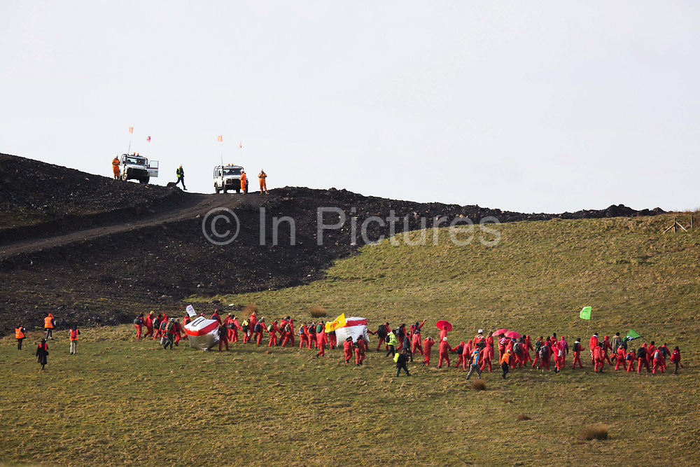 Hundreds of environmental activists stopping the open cast coal mine Ffos-y-Fran near Merthyr Tydfil, Wales from operating May 3rd 2016. The activists go unchallenged by employees of the mine, security and police.  The activists from Reclaim the Power wants the mine shut down and a moratorium on all future open coal mining in Wales. The group Reclaim the Power had set up camp near by and had over three days prepared the action and up to 300 activists all dressed in red went into the mine in the early morning. The activist were plit in three groups and carried various props signifying the red line in the sand, initially drawn in Paris at the COP21. The mine is one of the largest open cast coal mines in the UK and is run by Miller Argent who have to date extracted 5million tons of coal. The activists entered the mine unchallenged by any security or police and the protest went on peacefully till mid afternoon with no arrests made.  Open coal mining is hugely damaging to the local environment and  contributing to global climate change.