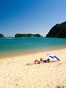 Young women sun on Tata Beach, Tata Bay, near Takaka, New Zealand