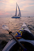 USA, Newport, RI - First person perspective from kayak with passing sailboat, Newport bridge in distance.