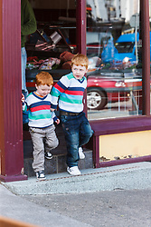 Boys dressed in striped shirts coming out of butcher shop, Westport, County Mayo, Ireland