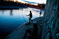 Several men fish along the Flint river behind Atwood Stadium at dusk. Flint, MI. 2011