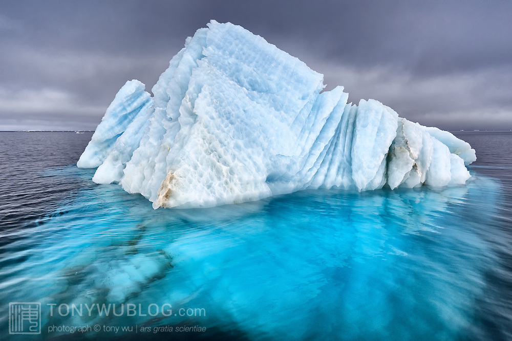 Natural ice sculpture floating at sea in Svalbard. The bulk of the ice is under the ocean surface.