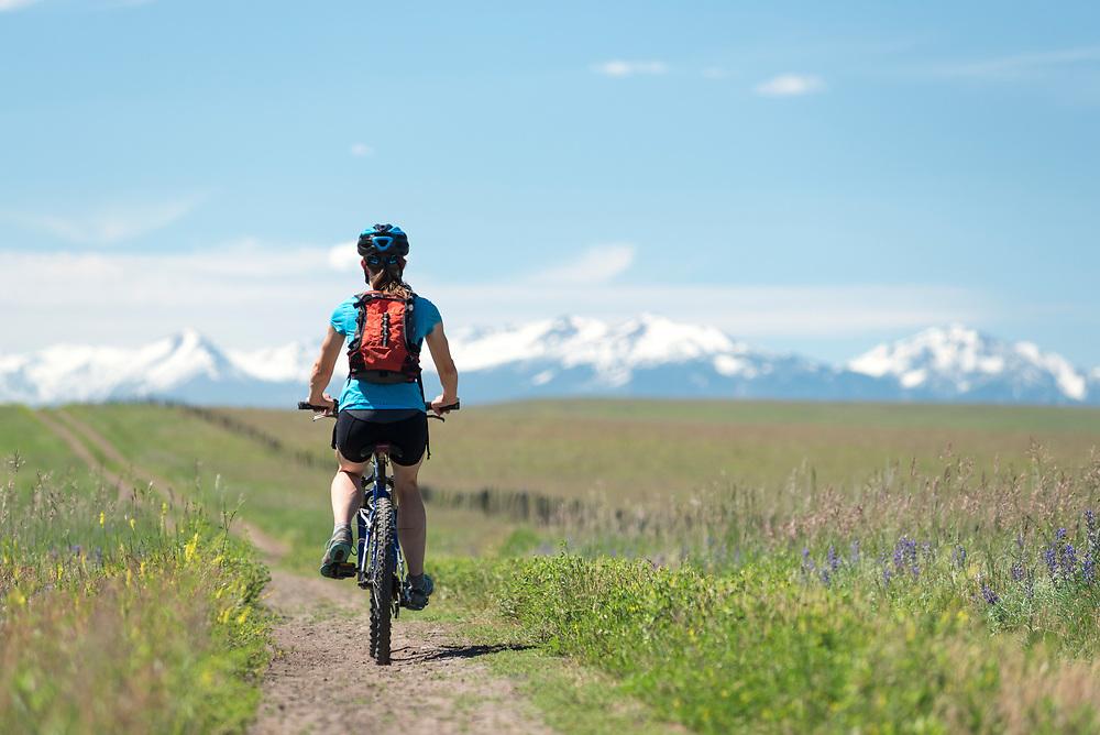 Woman mountain biking a road on the Zumwalt Prairie in Northeast Oregon.