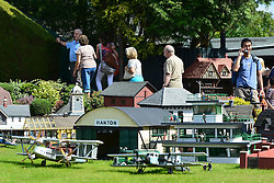 © Licensed to London News Pictures. 29/08/2013. Beaconsfield, UK People look at the model airport. People enjoy the sunshine and hot weather at Bekonscot Model Village in Berkshire today 29th August 2013. Bekonscot Model Village and Railway is the world's oldest and original model village, opening for the first time in 1929. With over 80 years of history, huge model railway, 1.5 acres of well kept gardens and finely detailed model buildings. Photo credit : Stephen Simpson/LNP