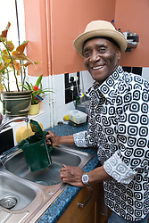 Older man at home in his kitchen filling the kettle,