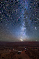 Thousands of stars forming the milky way galaxy are seen above a deep canyon in Utah. The Colorado River flows 2000 feet below the rim of Dead Horse Point into Canyonlands National Park. The bright light on the horizon is the planet Venus. There is no other object in the night sky brighter than Venus except for the moon. The clear weather, dry air, and dark skies make this area one of the best in the country for stargazing.<br /> <br /> Date Taken: 11/5/2013